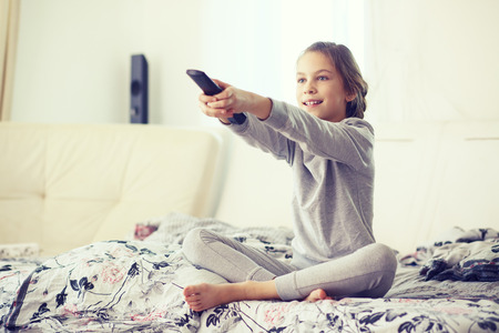 8 years old child watching tv, relaxed in parents bed in morning at home