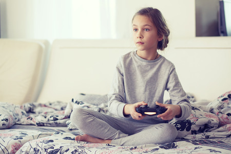 Child playing video game on tv in morning at parents bedroom at home