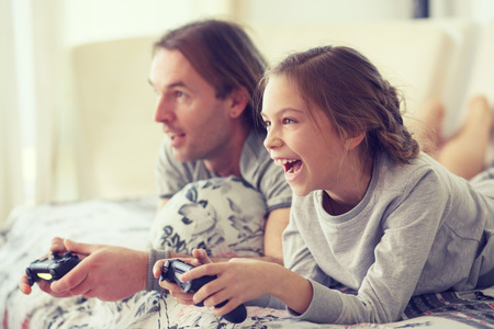 Child playing video game on tv with father in morning at bed at home Stock fotó