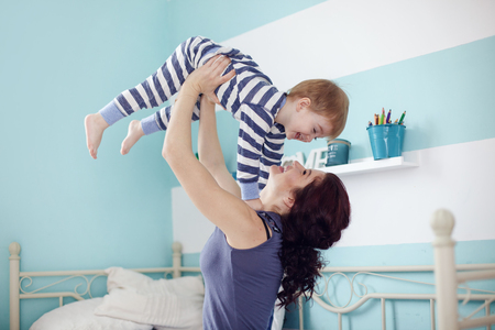 2 year old: Young mother playing with her 2 years old little son at the bedroom