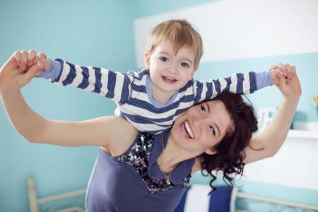 Jonge moeder speelt met haar 2 jaar oude zoontje op de slaapkamer Stockfoto