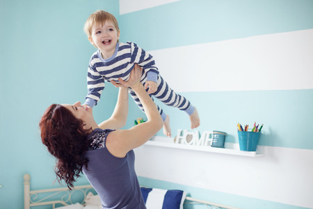 2 years old: Young mother playing with her 2 years old little son at the bedroom