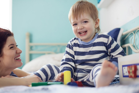 Young mother playing with her 2 years old little son at the bedroom photo
