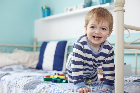 2 years old toddler playing with toys at the bedroom photo