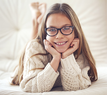 8 years old: Home portrait of 8 years old school girl wearing glasses resting on the sofa, looking at camera