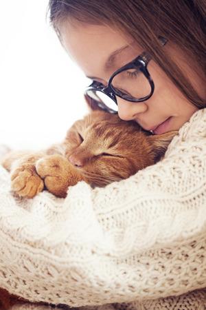 Nette rote Katze schläft Erwärmung in Strickpullover auf Händen seines Besitzers Standard-Bild