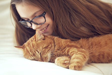Cute ginger cat sleeps near kid girl on the sofa Фото со стока - 37827229