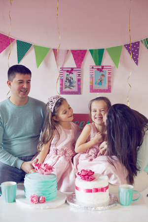 Family celebrating birthday princess party of two 6 years old children photo
