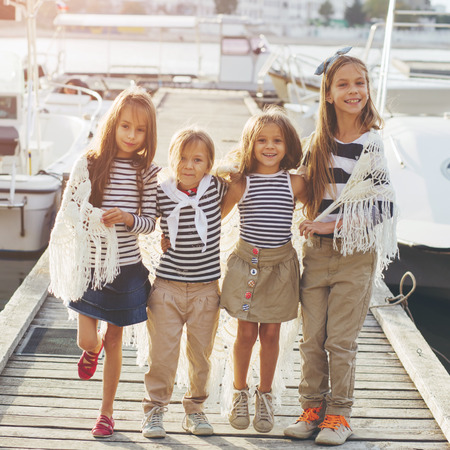 Group of fashion kids wearing navy clothes in marine style walking in the sea port Stock Photo