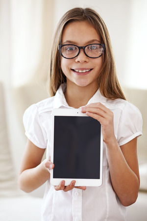 eight years old: 8 years old school girl wearing glasses holding tablet pc