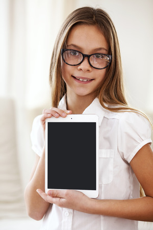 8 years old: 8 years old school girl wearing glasses holding tablet pc