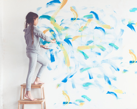 preteen girls: 8 years old girl painting the wall at home, Instagram style toning
