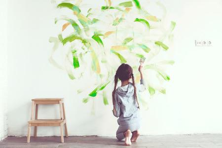 manos sucias: Ni�a de 8 a�os pintando la pared en casa