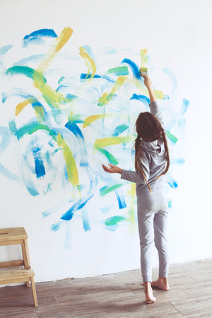 8 years: 8 years old girl painting the wall at home