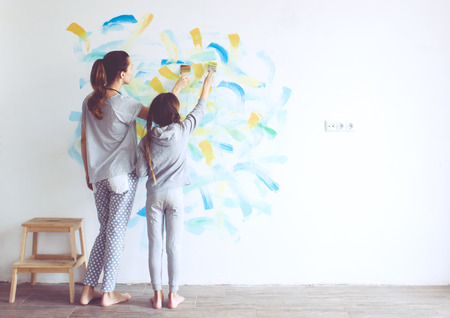 parent child: 8 years old girl painting the wall at home