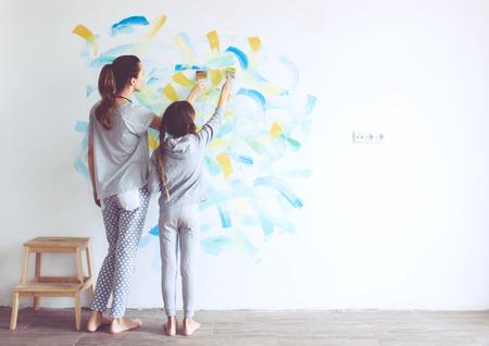 pintor: Niña de 8 años pintando la pared en casa