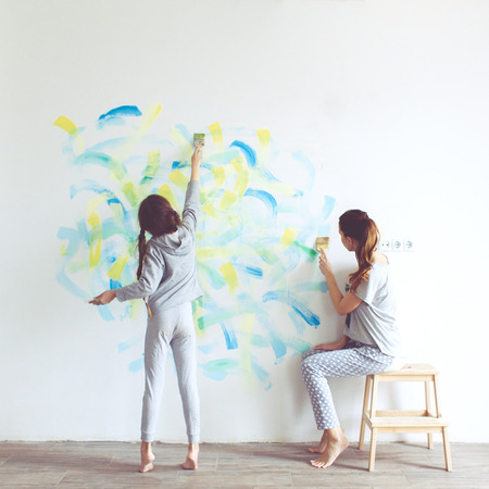 children painting: 8 years old girl painting the wall at home, Instagram style toning