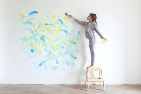 8 years old girl painting the wall at home Stock Photo