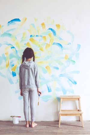 8 years old girl painting the wall at home Фото со стока - 38198714