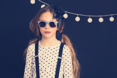 ni�o modelo: Moda foto de la joven ni�o inconformista vistiendo ropa fresca y gafas de sol de pie sobre la pared oscura