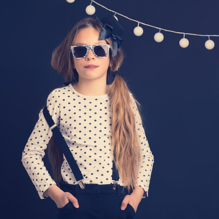 glasses model: Fashion photo of young hipster child wearing cool clothes and sunglasses standing over dark wall  Stock Photo