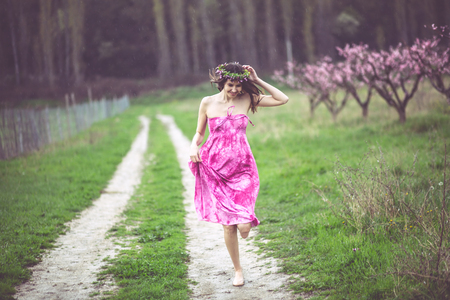 Young beautiful girl walking in the rain at blooming spring garden photo