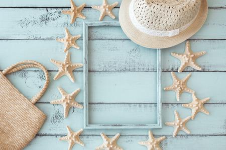 Zomer strand decoratie: zeesterren fotolijst met stro hoed en handtas op mint houten achtergrond