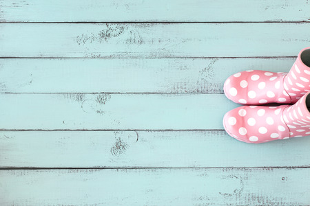 Pink polka dot rain boots on mint blue shabby chic wooden background, top view point