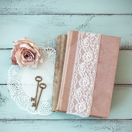 Old books with lace, rose and keys on shabby chic mint background, top view point