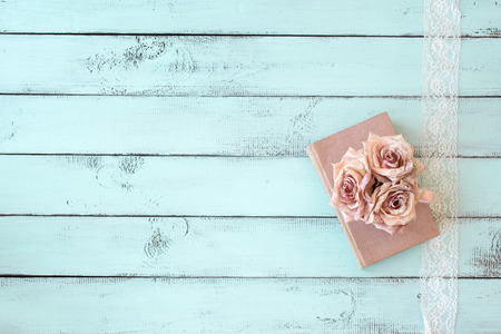 blue romance: Old books with lace, rose and keys on shabby chic mint background, top view point