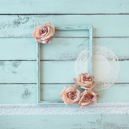 shabby chic background: Wooden photo frame with lace and flowers on mint shabby chic background