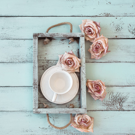 aqua flowers: Vintage wooden tray with porcelain teacup and rose buds on shabby chic mint background, top view point Stock Photo