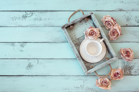 Vintage wooden tray with porcelain teacup and rose buds on shabby chic mint background, top view point Stock Photo
