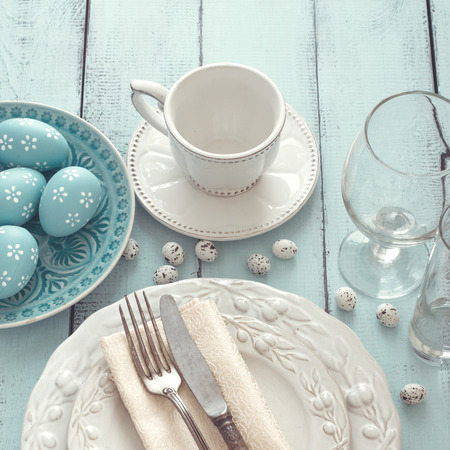 Easter table setting with holiday decor on mint wooden background, top view point