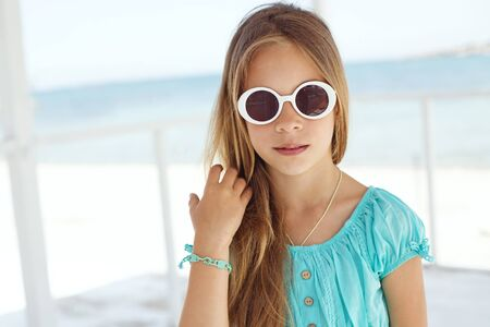 preteens beach: Preteen child wearing aqua blue fashion clothes resting at the beach in summer Stock Photo