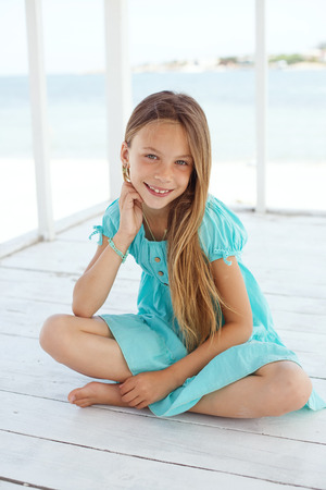 Preteen child wearing aqua blue fashion clothes resting at the beach in summer Stock Photo