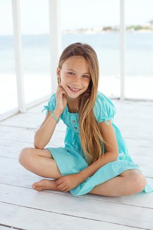 Preteen kind draagt aqua blauw mode kleding rusten op het strand in de zomer