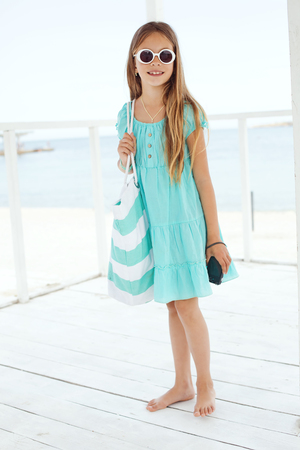 preteens girl: Preteen child wearing aqua blue fashion clothes resting at the beach in summer Stock Photo