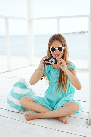 preteens girl: Preteen child resting and taking photos at the beach in summer