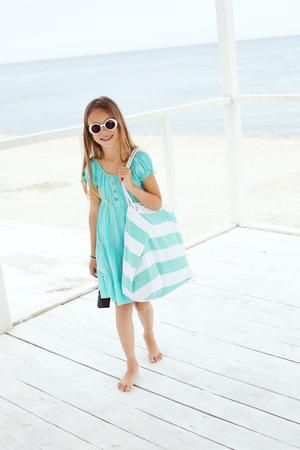 playa vacaciones: Ni�o preadolescente llevaba ropa azul aqua moda descansando en la playa en verano