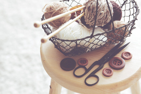 yarn: Vintage knitting needles, scissors and yarn inside old wire basket on wooden stool, still life photo with soft focus Stock Photo