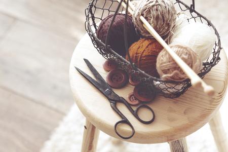 gomitoli di lana: Ferri da maglia d'epoca, forbici e filati all'interno di vecchio cestello su sgabello di legno, ancora foto di vita con soft focus Archivio Fotografico