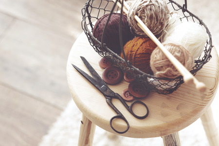 Vintage knitting needles, scissors and yarn inside old wire basket on wooden stool, still life photo with soft focus Stockfoto