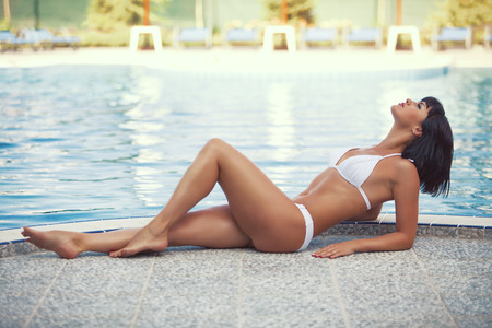 Portrait of beautiful young woman with fine figure resting at beach in summer photo