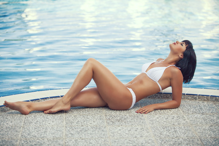 fine legs: Portrait of beautiful young woman with fine figure resting at beach in summer Stock Photo