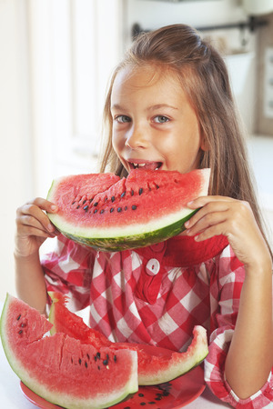 8 years old: 8 years old child eating watermelon at home