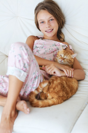 preteens: Preteen school girl of 8-9 years old with her pet resting on a sofa at home