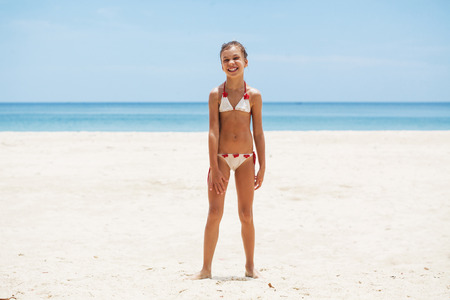 nine years old: Child posing on a tropical beach during summer vacations