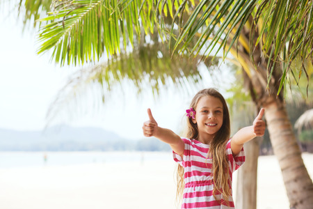 8 years old girl on the tropical palm beach in Thailand in summer