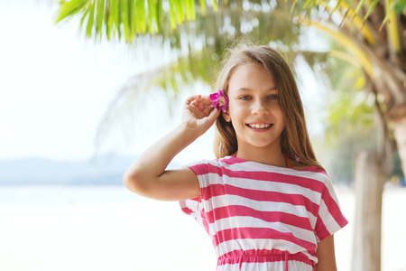 8 years: 8 years old girl on the tropical palm beach in Thailand in summer, holding orchid flower in her hair